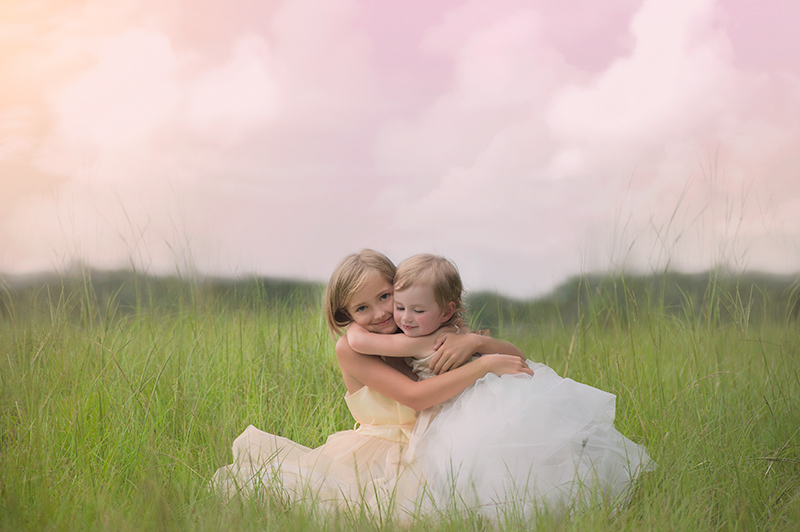 two sisters hugging in a field