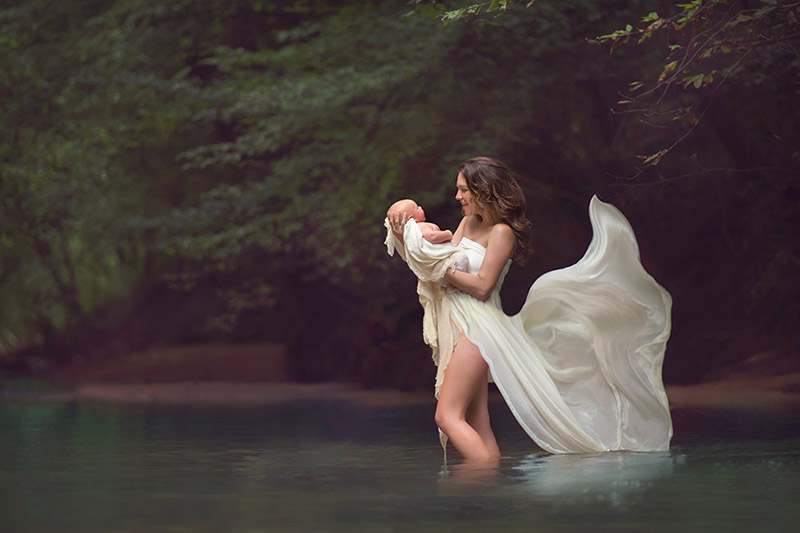 mom in the creek with baby with a large flowing dress