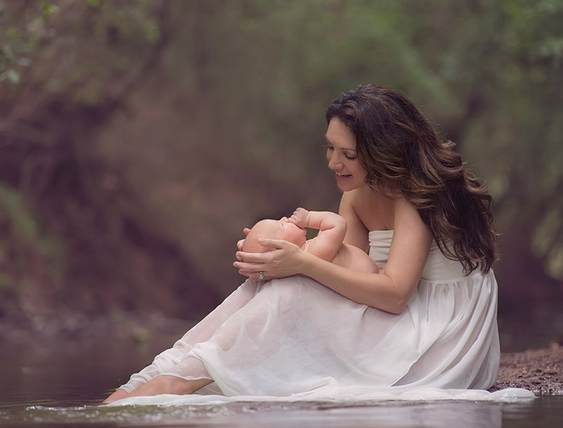 mother comforting her baby in the creek for a portrait