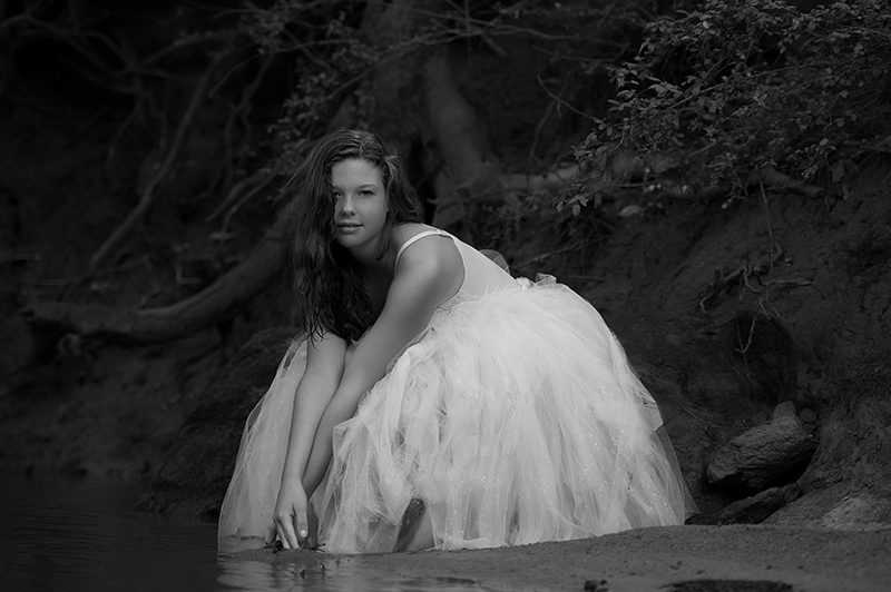 black and white photo of girl in the creek