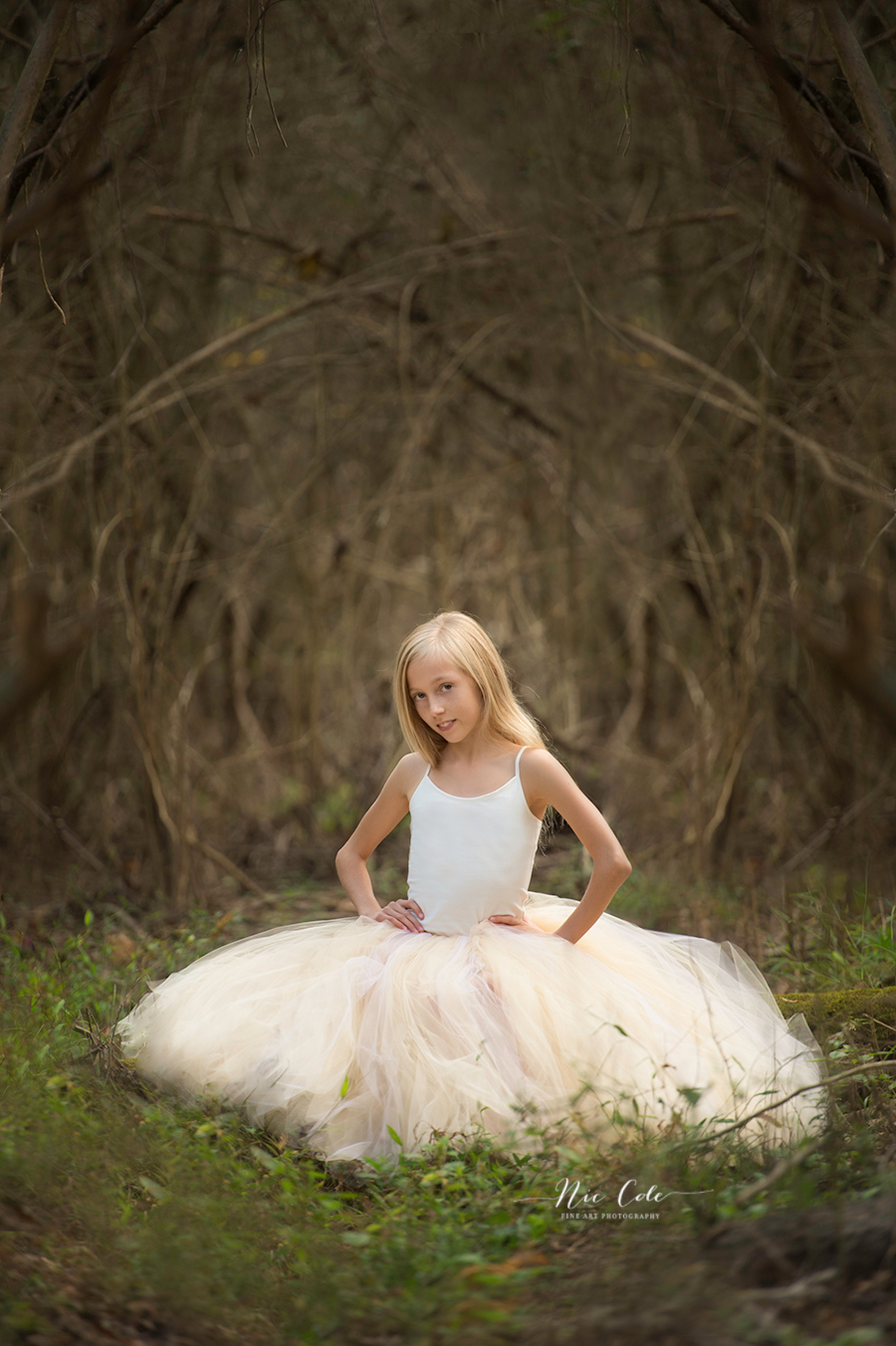 blonde child in woods wearing a tutu