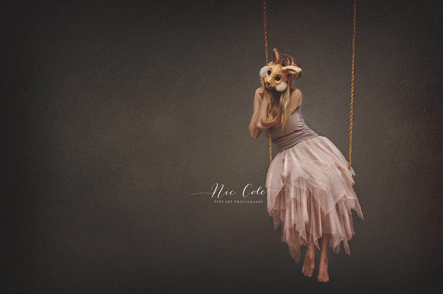 woman with bunny mask on swing