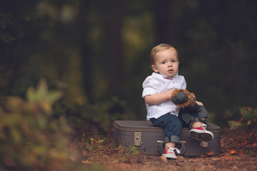 Child-portrait-charlotte-baby-photographer-boy-sitting-on-suitecase-in-woods